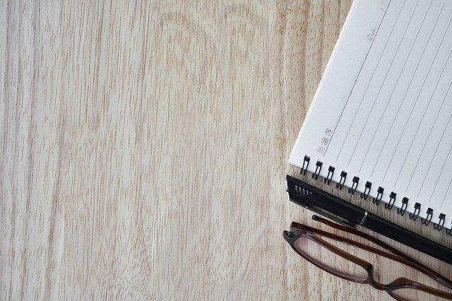 En notesbog og nogle briller ligger på et bord.